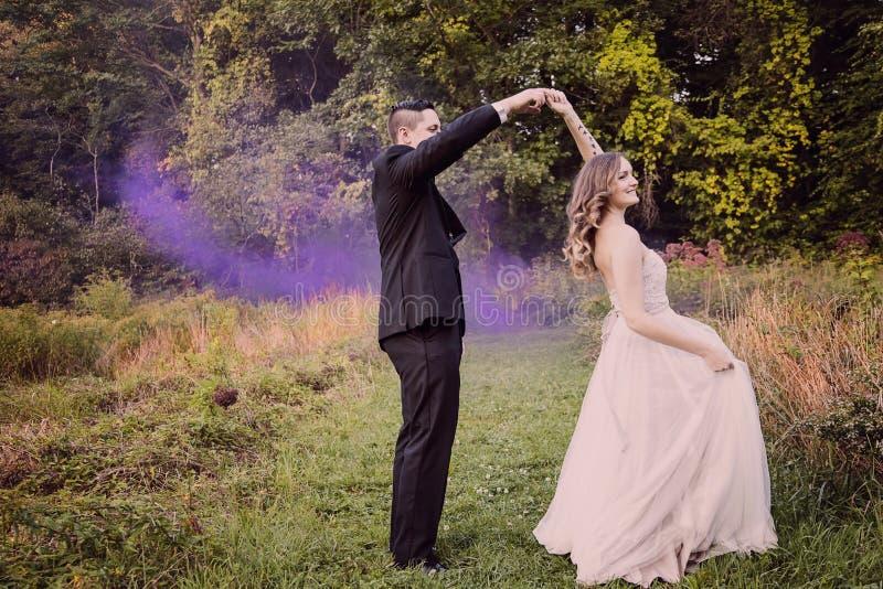 Brud- och brudgumdansen i skog med lilor röker royaltyfri fotografi