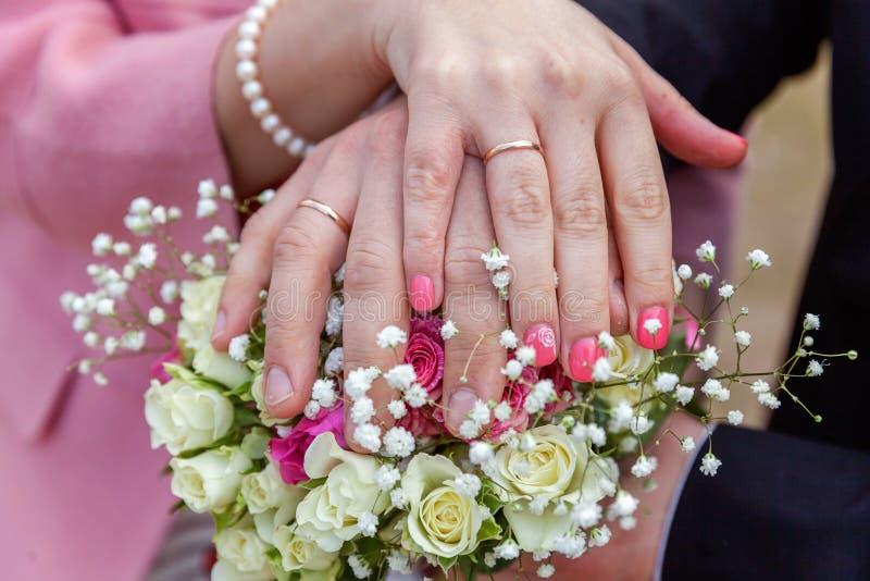 Brud- och brudgumhänder med vigselringar mot bakgrund av den brud- buketten av blommor royaltyfri foto