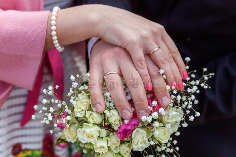 Brud- och brudgumhänder med vigselringar mot bakgrund av den brud- buketten av blommor arkivbilder