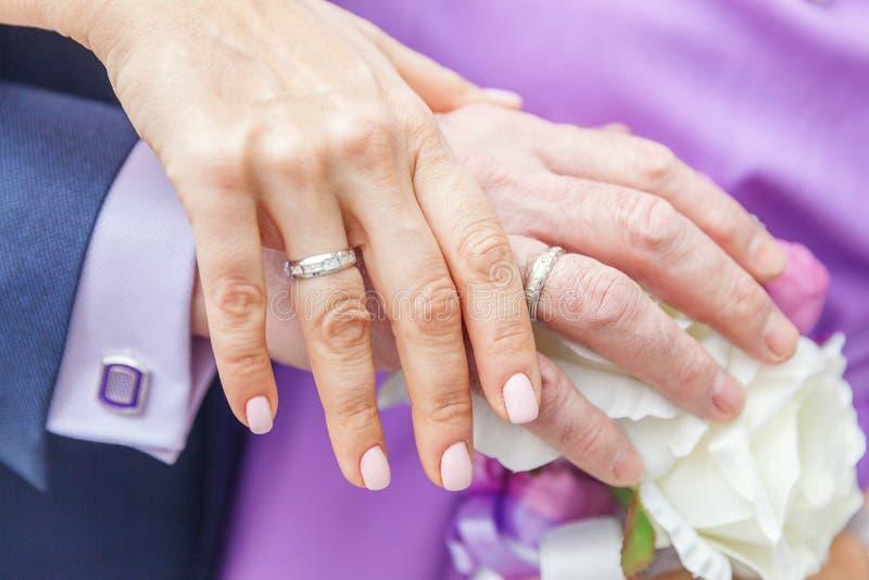 Brud- och brudgumhänder med vigselringar mot bakgrund av den brud- buketten av blommor royaltyfria foton