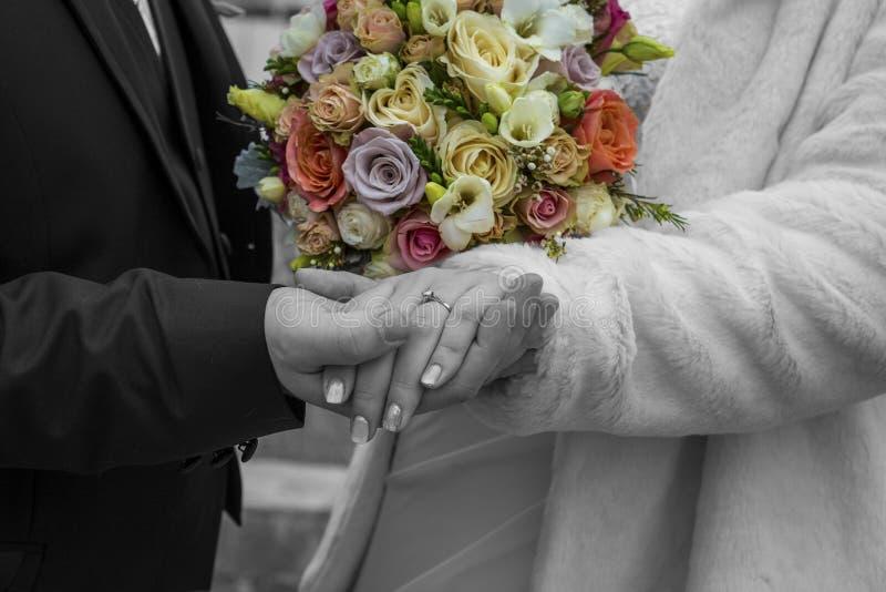 Brud- och brudgumhållhänder i en svartvit färgrik bukett av rosor royaltyfria foton