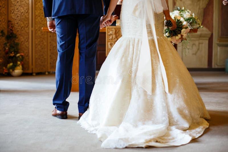 Brud- och brudgumhållhänderna framme av altaret royaltyfri fotografi