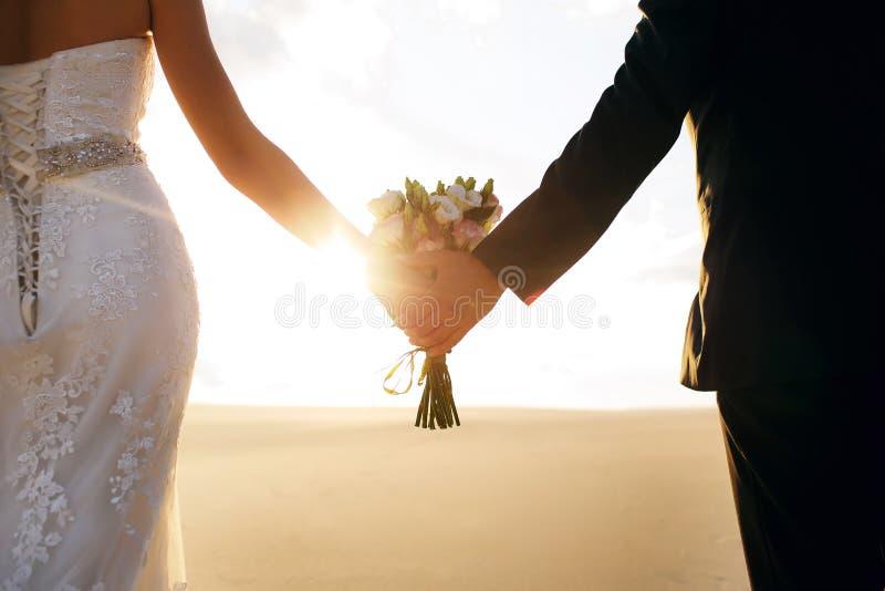 Brud- och brudgumhållhänderna, i händerna av en härlig bukett, paren står i öknen på solnedgången royaltyfria foton