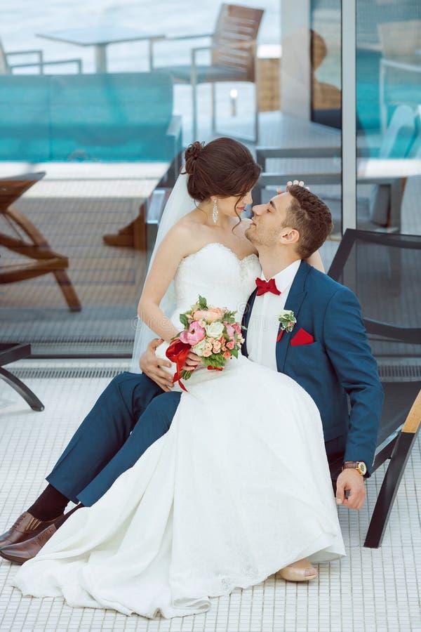Brud- och brudgumidoors på pölen royaltyfria bilder