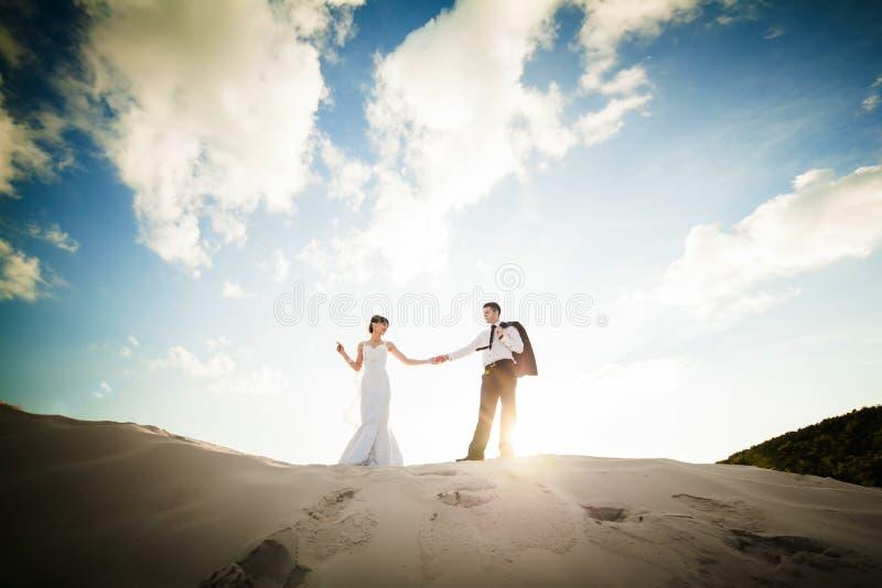 Brud- och brudguminnehavhänder och spring till och med sanden på th royaltyfri bild
