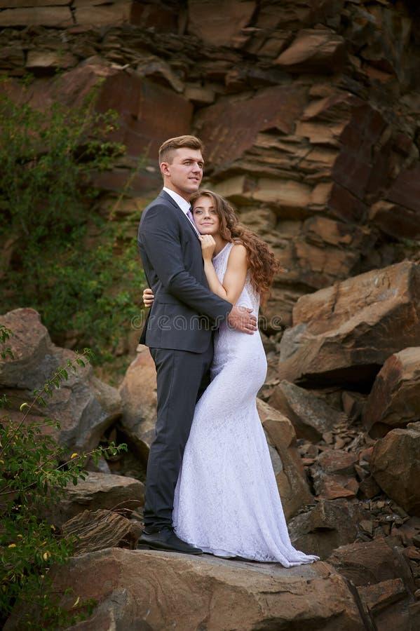 Brud- och brudgumomfamningen på en bakgrund av löst vaggar i bergen royaltyfri foto
