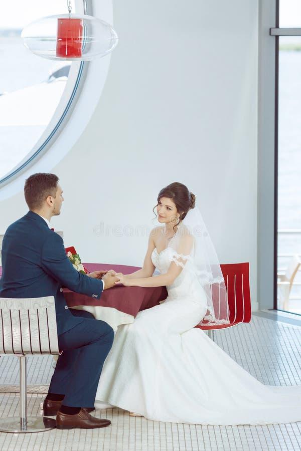 Brud- och brudgumsammanträde i inomhus kafé royaltyfri foto