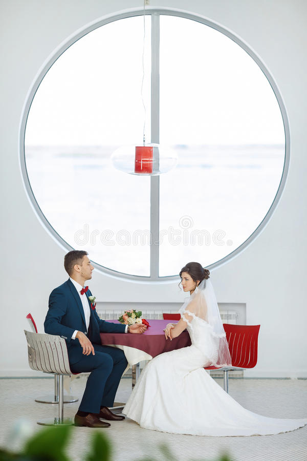 Brud- och brudgumsammanträde i inomhus kafé arkivfoto