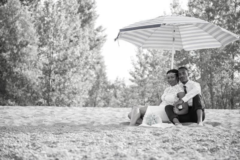 Brud- och brudgumsammanträde i sand på stranden under paraplyet arkivbilder