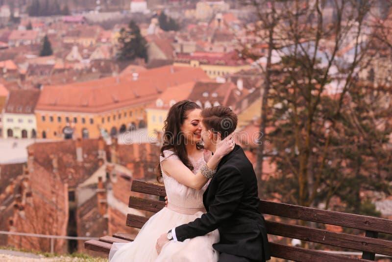 Brud- och brudgumsammanträde på en bänk i staden arkivfoto