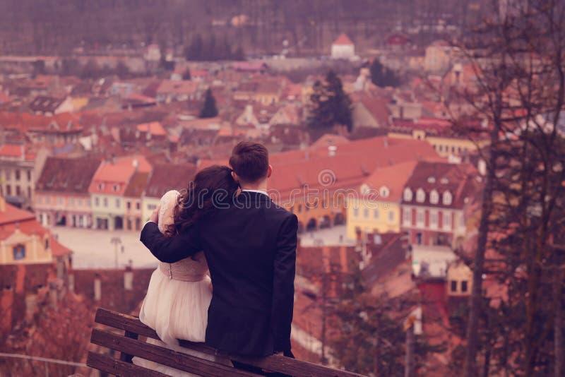 Brud- och brudgumsammanträde på en bänk i staden royaltyfri foto