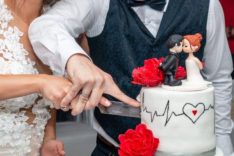 Brud- och brudgumsnittbröllopstårta royaltyfri fotografi