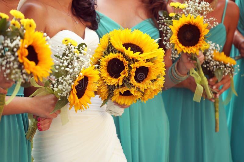 Brud och brudtärnor med solrosbuketten arkivfoto