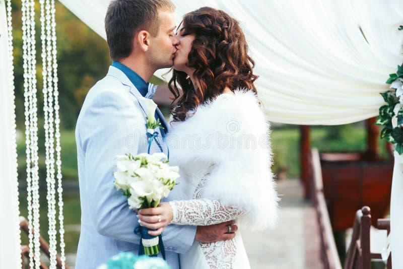 Brud och fiance som framtill kysser av bröllopaltaret royaltyfri fotografi