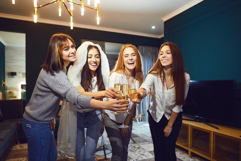 Brud och lyckliga brudtärnor som firar möhippan med exponeringsglaschampagne arkivbilder