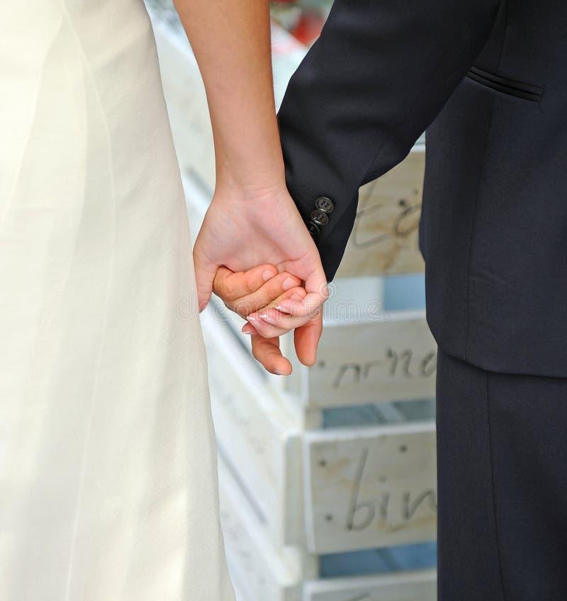 Brud- parinnehavhänder under deras bröllop royaltyfri fotografi
