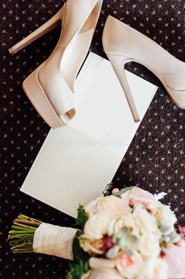 Brud- skor och bukett med inbjudan arkivfoto