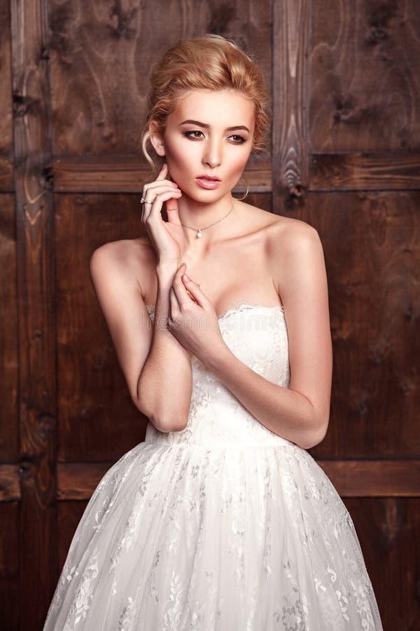 Brud- skytte för modeskönhet Härlig modebrud i bröllopsklänningen som framme poserar av träig bakgrund royaltyfri foto