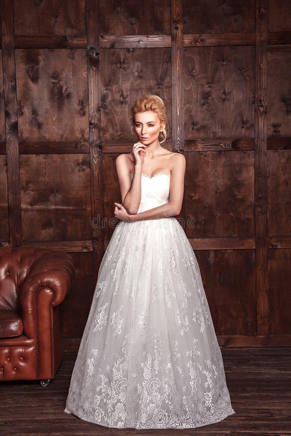 Brud- skytte för modeskönhet Härlig modebrud i bröllopsklänningen som framme poserar av träig bakgrund arkivbild