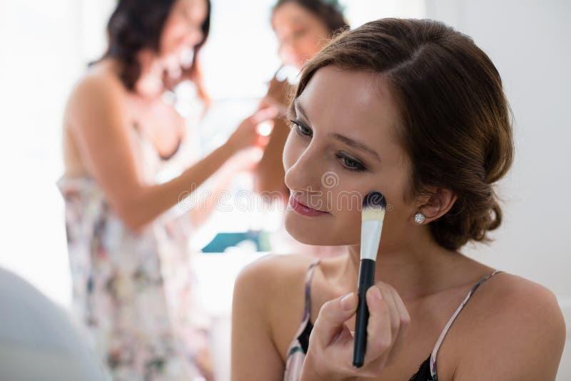 Brud som applicerar hennes makeup som gör hennes bröllopförberedelse royaltyfri fotografi