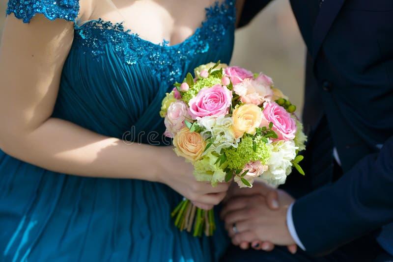 Brud som bär en blå klänning och brudgum på bröllopet med fokusen på bruds händer som rymmer en stor rund bukett arkivbild