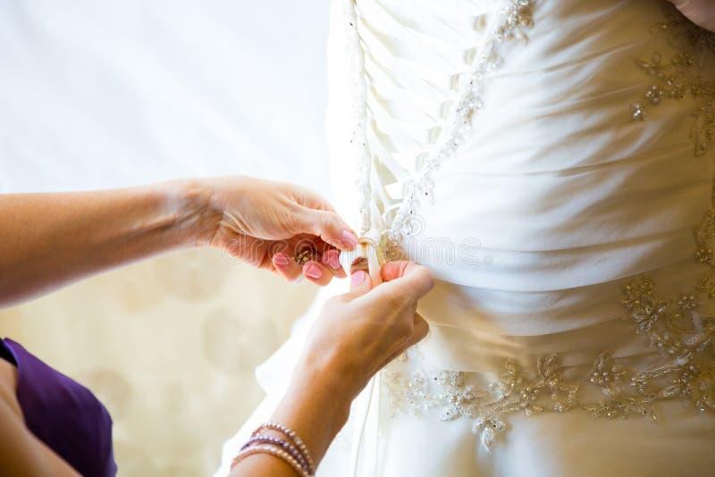 Brud som får på klänningen arkivbild