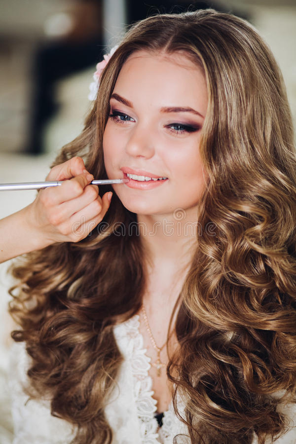 Brud som gör makeup i morgonen i ett rum sminkkonstnär som gör yrkesmässigt smink av den unga kvinnan Sminkkonstnär fotografering för bildbyråer