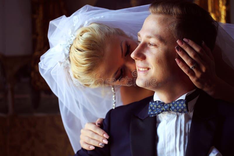 Brud som kysser brudgummen i hotellet fotografering för bildbyråer