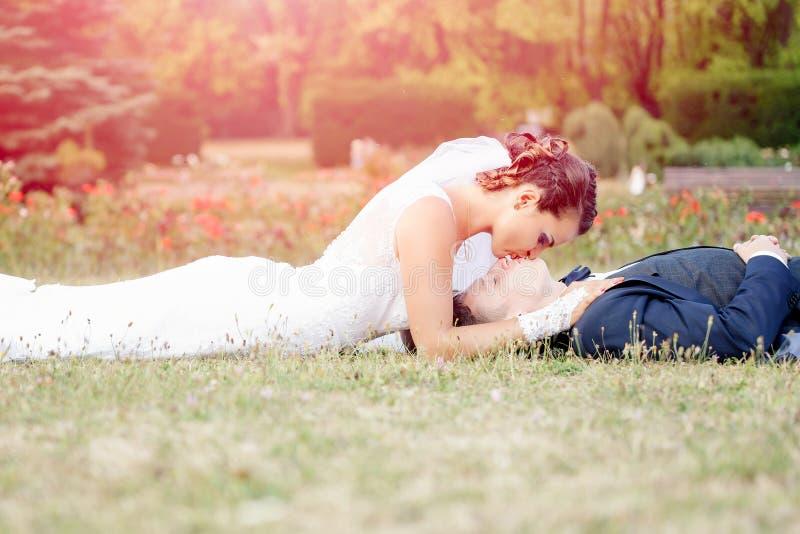 Brud som kysser den liggande brudgummen på äng royaltyfri fotografi