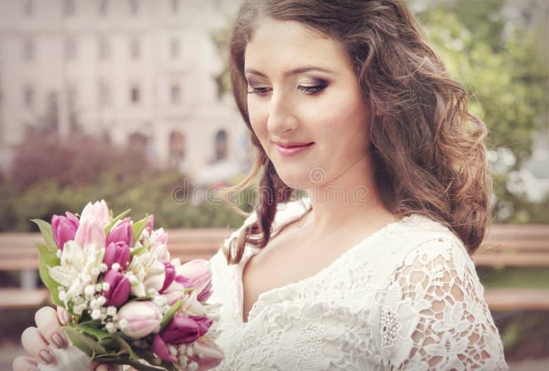 Brud som ler, med bröllopbuketten royaltyfri foto