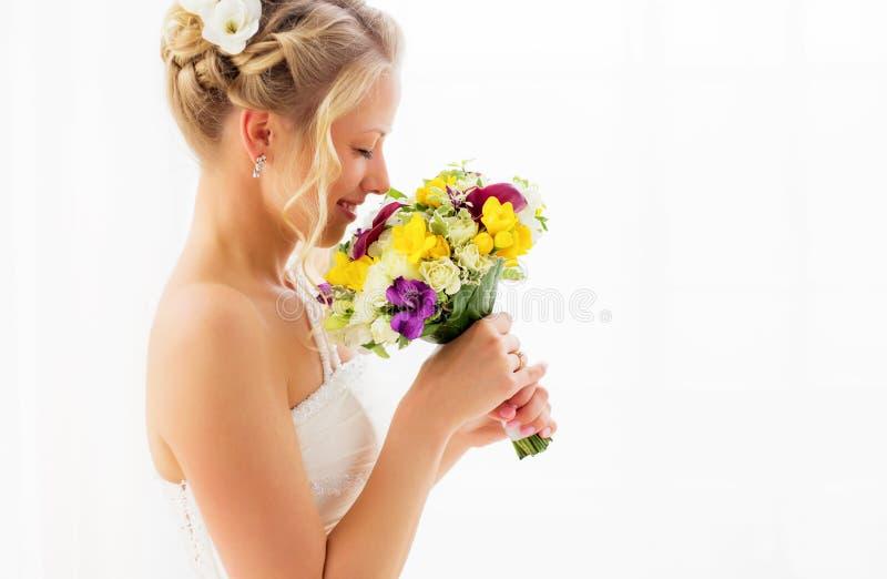 Brud som luktar hennes bröllopbukett arkivbilder