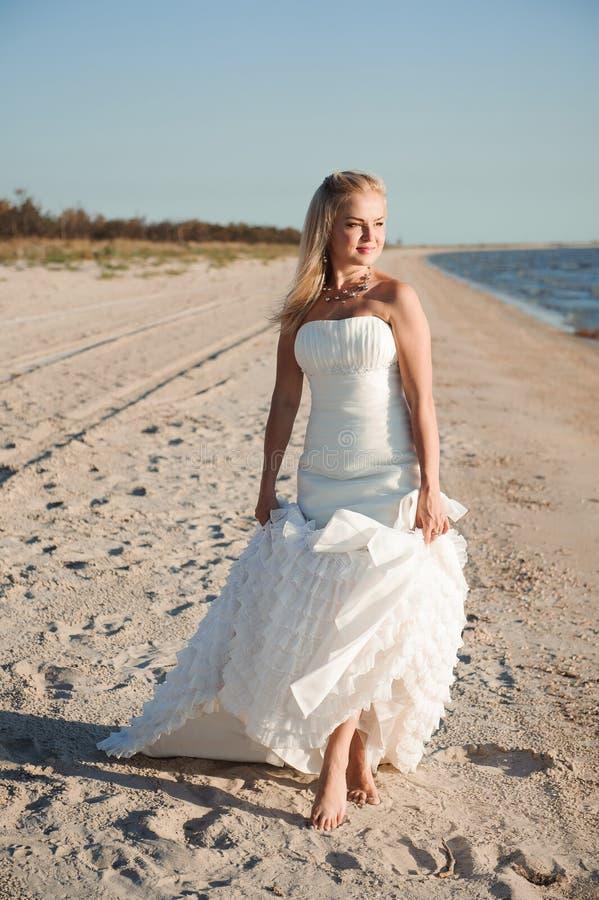 Brud som promenerar havskusten som bär den härliga bröllopsklänningen royaltyfri bild