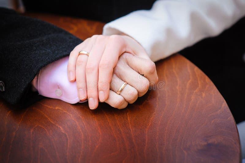 Brud som rymmer brudgummens hand på tabellen arkivfoton