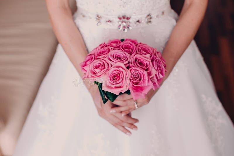 Brud som rymmer den ljusa bröllopbuketten av den rosa roscloseupen royaltyfria foton