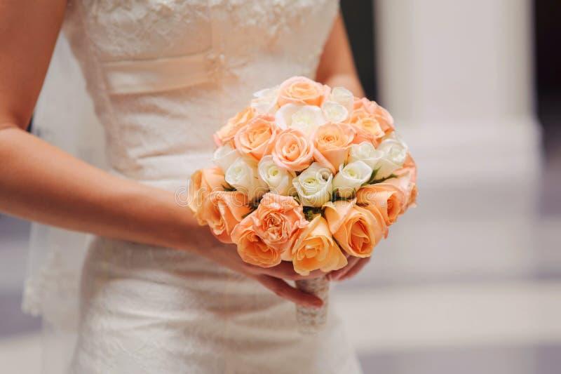 Brud som rymmer en bröllopbukett arkivfoton