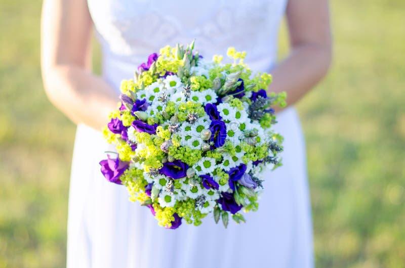 Brud som rymmer en bukett av blommor i en lantlig stil på äng för fokusförgrund för 3 bukett bröllop royaltyfri bild