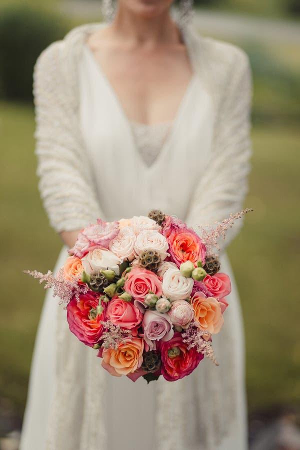 Brud som rymmer en bukett av blommor i en lantlig stil som gifta sig bo royaltyfria foton