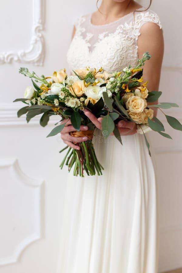 Brud som rymmer en bukett av blommor i en lantlig stil som gifta sig buketten arkivbild