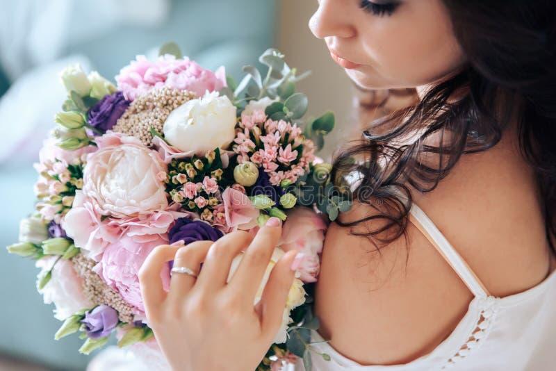 Brud som rymmer en bukett av blommor i lantlig stil som gifta sig arkivfoton