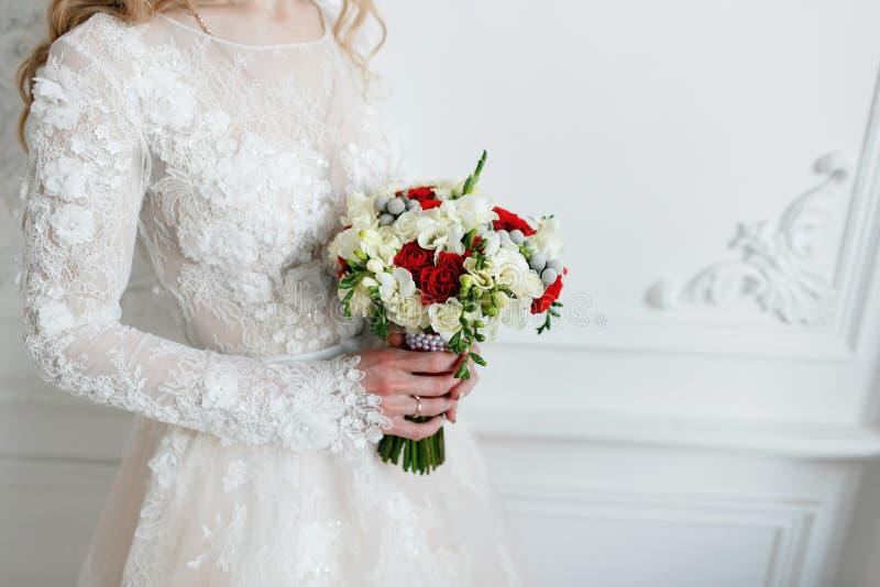 Brud som rymmer upp brud- bukettslut röda och vita rosor, freesia, brunia dekorerade i sammansättning arkivfoton