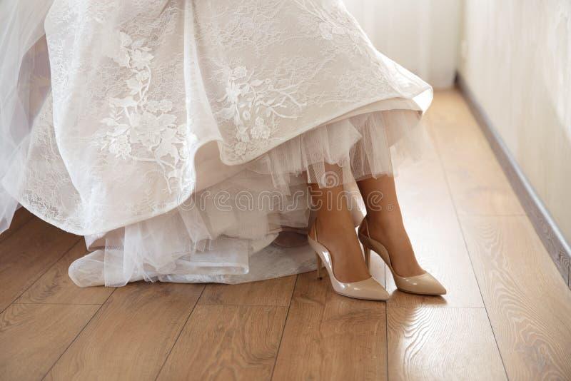Brud som sätter på att gifta sig skor hemma, var hon får klar - bärande vit klänning i ett ljust rum med trä royaltyfri bild