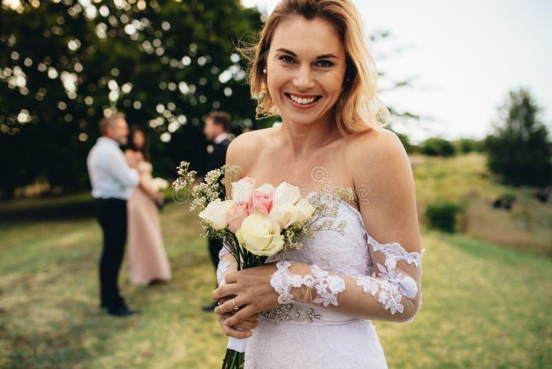 Brud som ser lycklig på brölloppartiet royaltyfri fotografi