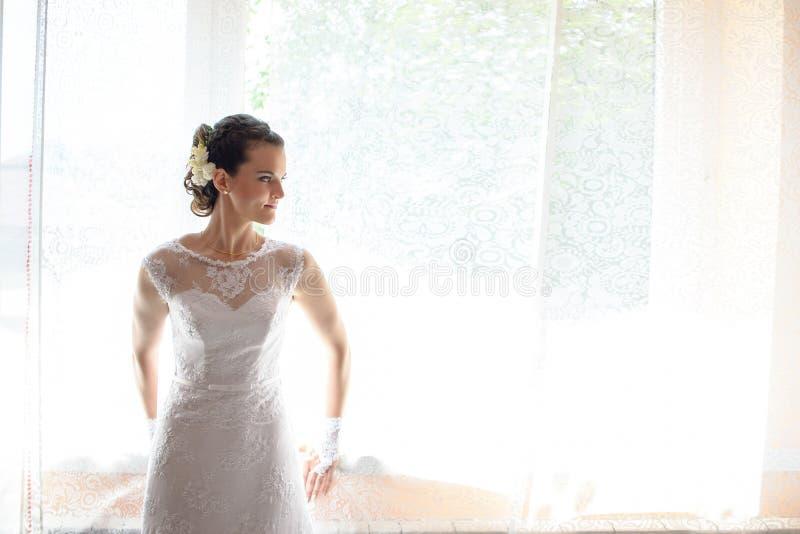 Brud som ser till och med fönstret royaltyfri fotografi