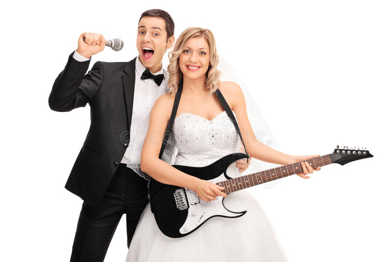 Brud som spelar gitarren och brudgumunderteckningen arkivfoton