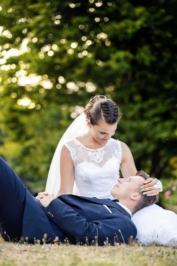 Brud som trycker på försiktigt brudgummen royaltyfri bild