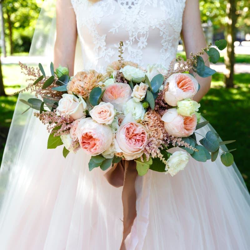 Brud som utomhus rymmer den härliga stora buketten av rosor arkivbild