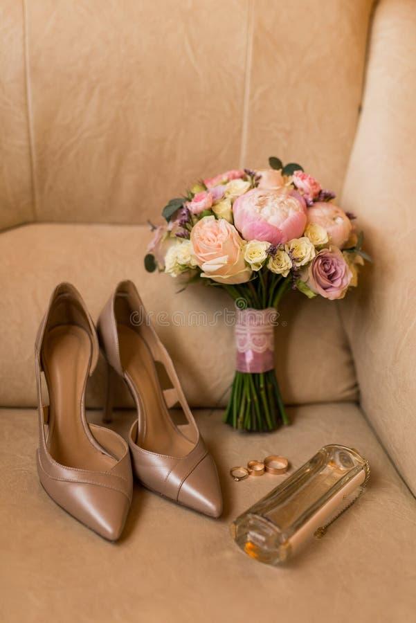 Brud- tillbehör: Bröllopbukett med den rosa pionen, guling, rosa rosor och grönska, eleganta brud- beigaskor, guld- cirklar, pe arkivfoton