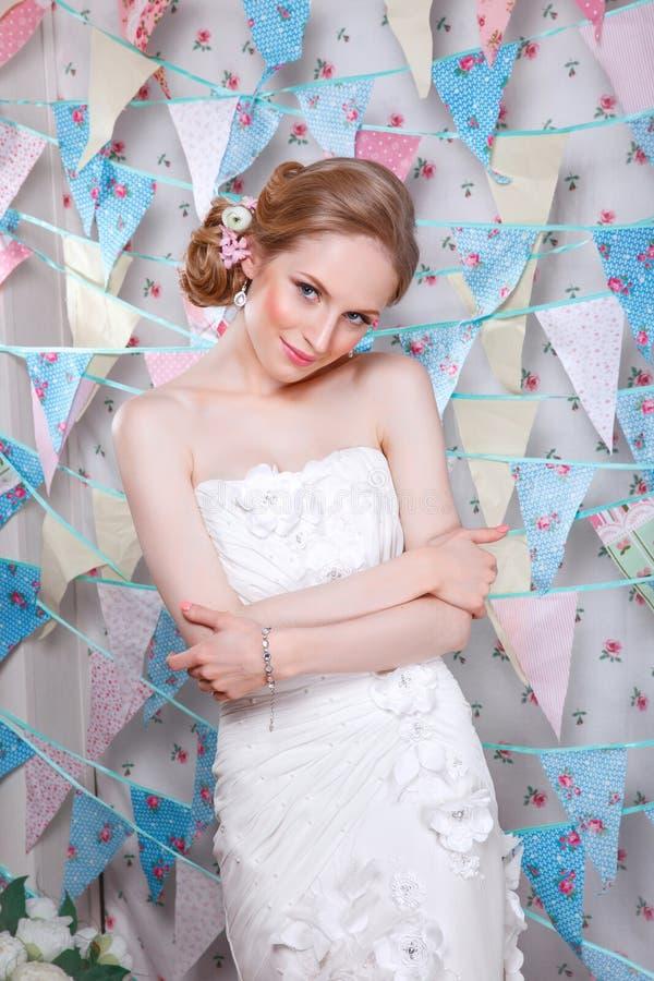 Brud Ung modemodell med perfekt hud och smink, blommor i hår Härlig kvinna med makeup och frisyr i sovrum royaltyfri fotografi