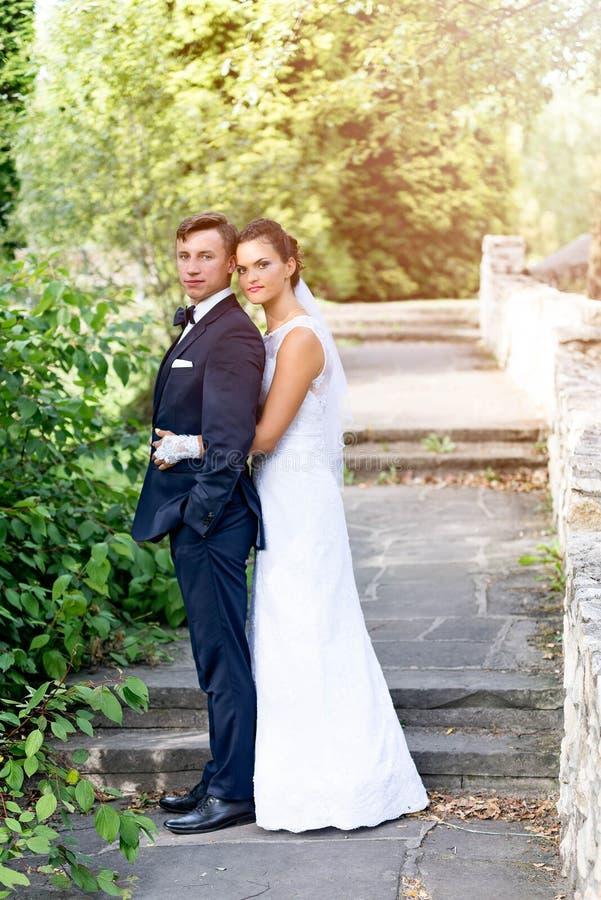 Brudanseendet bak brudgum och kramar honom royaltyfri bild