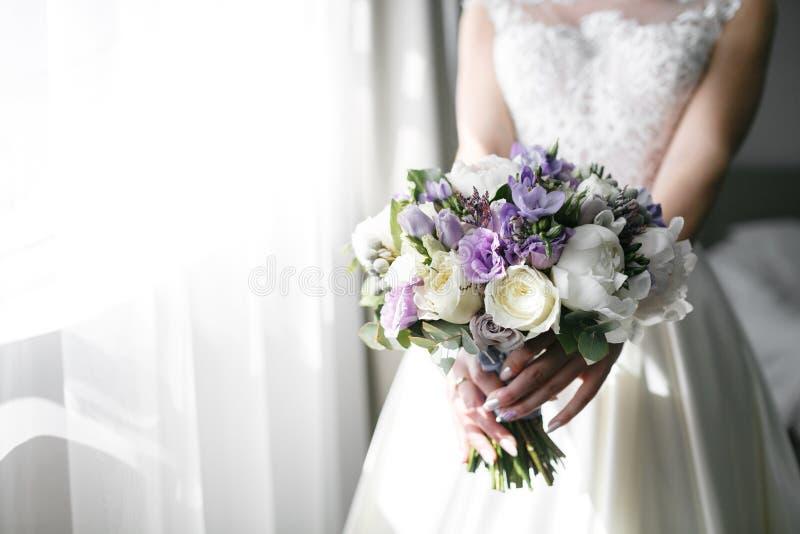 Brudar som gifta sig buketten med pioner, freesia och andra blommor i händer för kvinna` s Ljus och lila vårfärg Morgon fotografering för bildbyråer